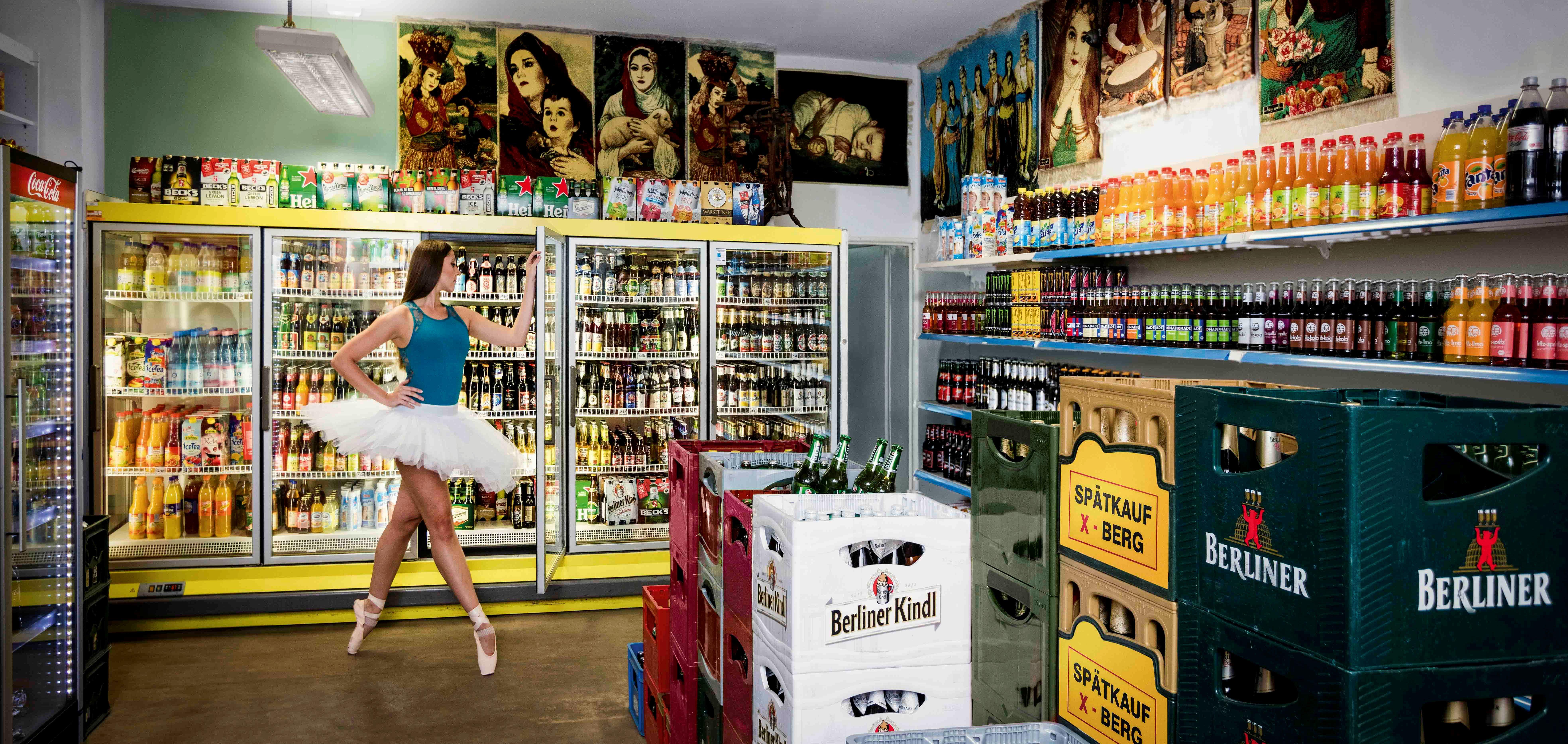"""Fotoprojekt """"Stages of Berlin"""" mit Ballett-Tänzerinnen in Berlin von Fotograf und Filmer Gero Breloer. November 2016: Ekaterina Herber steht im X-Berg Späti auf der Skalitzer Straße 52 (Ortsteil Kreuzberg) an den Kühlschränken unter kurdischen Wandteppichen von Späti-Besitzer Diyari. Schätzungen zufolge gibt es mehr als 1000 Spätverkaufsstellen in Berlin, die außerhalb der üblichen Ladenöffnungszeiten geöffnet sind. Foto: Gero Breloer www.breloer.com"""